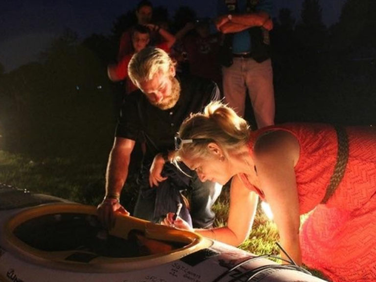 Gold Star mom, Debbie Lee, signing the kayak for the Swim for the Sacrifice challenge